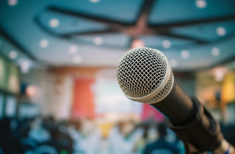 Ein schwarzes Mikrofon vor verschwommenem Hintergrund